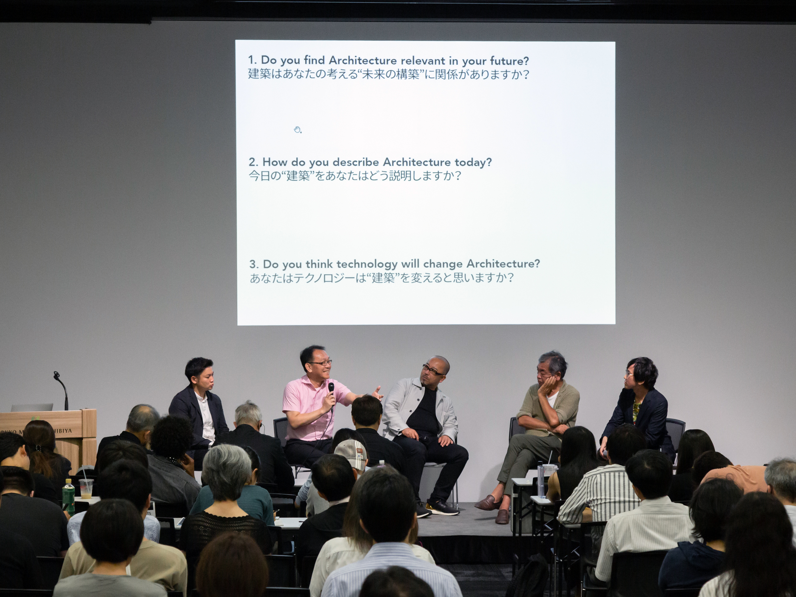 A panel of five people sitting in front of a screen with English and Japanese text