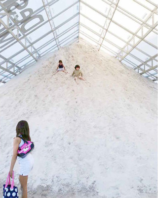 Image of children playing on a sand mound in the Tentpile pavillion