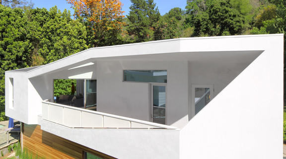 Image of an addition to a white angular house surrounded by trees in Beverly Hills, California.