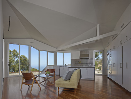 Image of the living space and kitchen inside the Vortex House, with an angular ceiling looking out across the Malibu Hills.