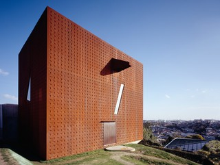 Image of a rust colored, metal clad structure on a hilly site in Shiogama, Japan, with a view of the Pacific Ocean.