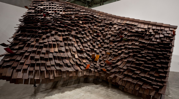 Images of Rawhide installation in the SCI-Arc Gallery. A scale model of the construction of the roof of a house with brown curled cedar shingles.