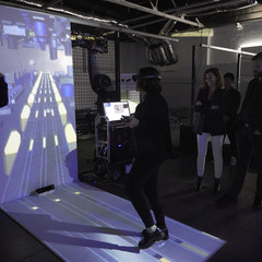 A woman with a VR headset in front of a screen projecting an immersive experience