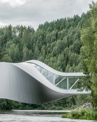 Image of a twisted building / bridge over a river in a forest.