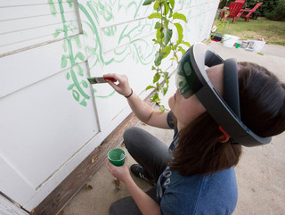 Image of a woman using a VR tool to paint a mural on a wall