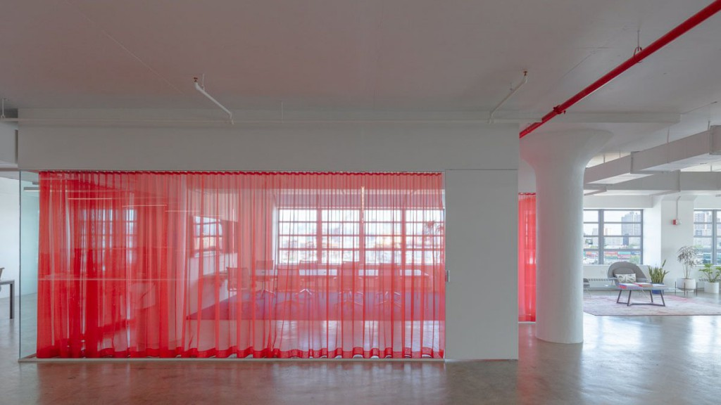 Image of a modern office space with a red curtain dividing the space