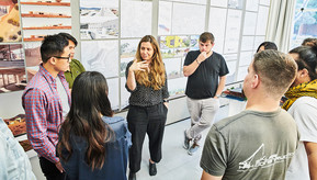 Image of faculty chatting with students